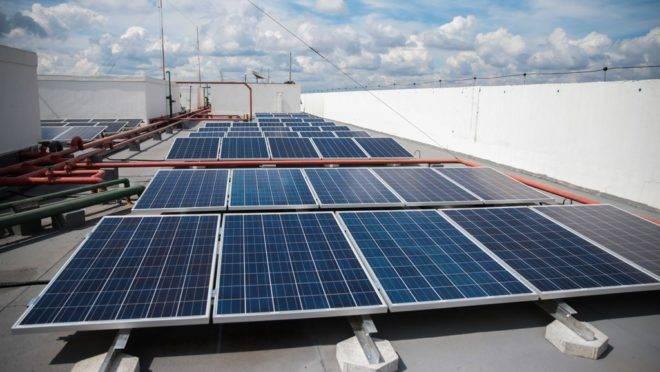Placas solares no terraço de um prédio.