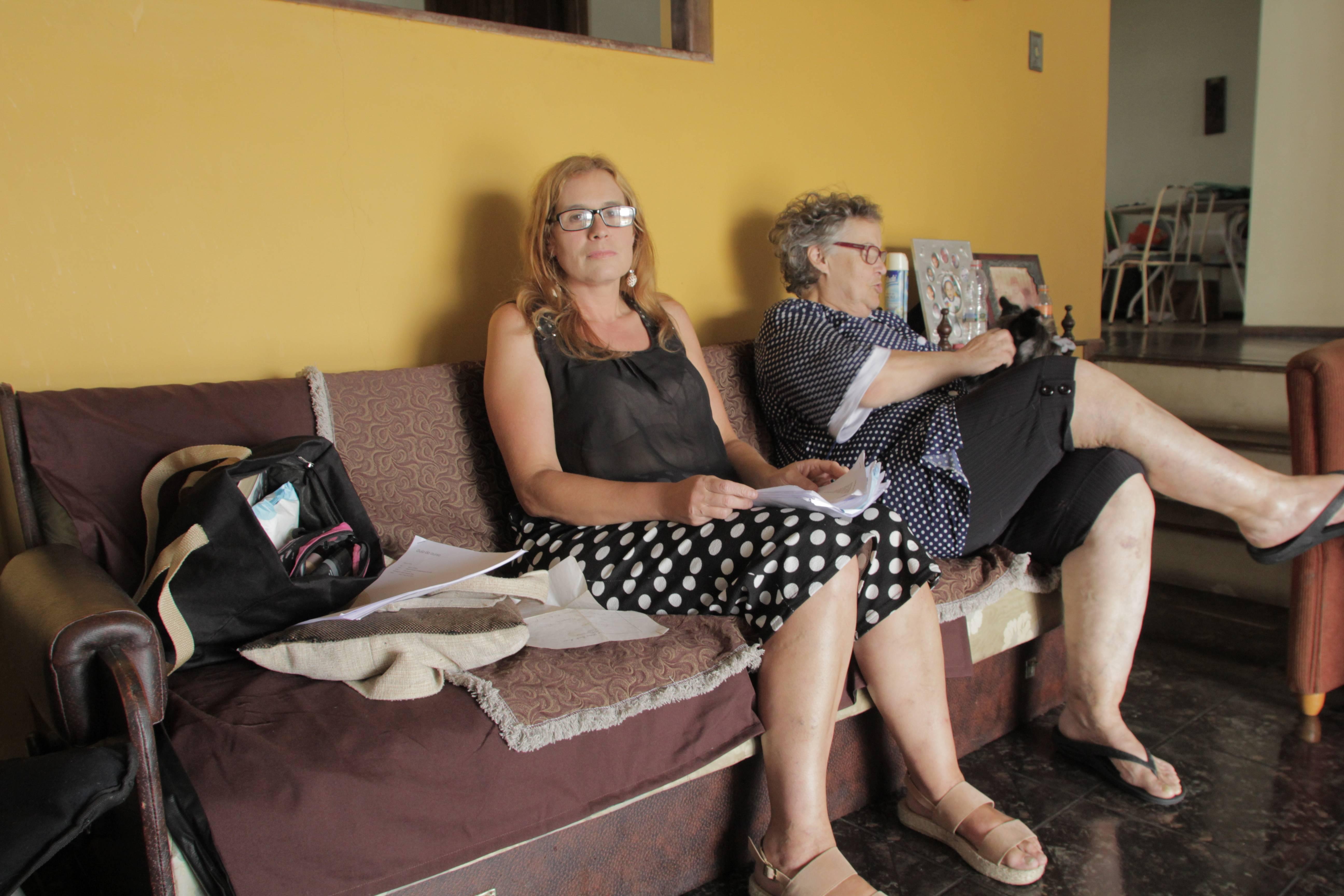 Kelly, com a sua mãe Rosaneide Dreher Mesquita, mostram os laudos médicos que carregam a todas as consultas médicas e internações. Foto: Amanda Milléo / Gazeta do Povo
