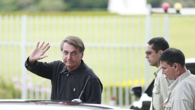 Presidente Jair Bolsonaro cumprimenta populares na entrada do Palácio da Alvorada na manhã desse sábado (18). Foto: José Cruz/Agência Brasil