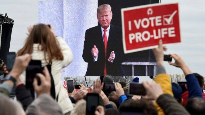 "Pro-life demonstrators listen to US President Donald Trump as he speaks at the 47th annual ""March for Life"" in Washington, DC, on January 24, 2020. – Trump is the first US president to address in person the country's biggest annual gathering of anti-abortion campaigners. (Photo by OLIVIER DOULIERY / AFP)"