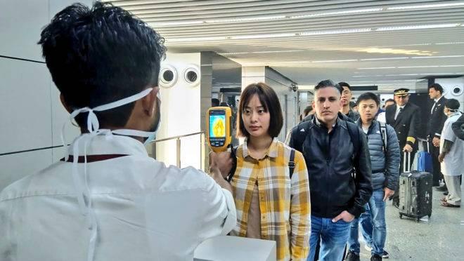 Medição de temperatura de passageiros originários da China na chegada ao aeroporto de Calcutá