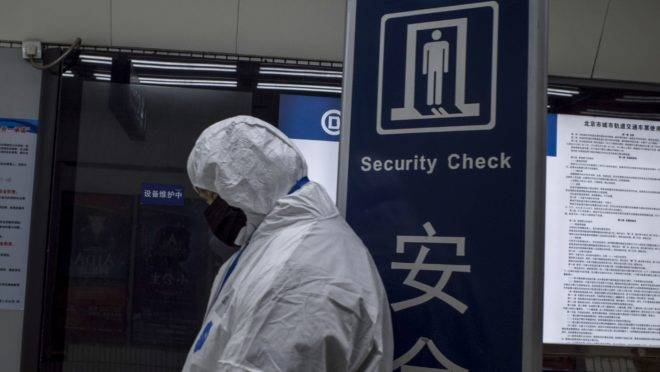 Agentes com roupas protetoras estão monitorando passageiros em estações de metrô de Pequim, em tentativa de conter a disseminação do coronavírus.