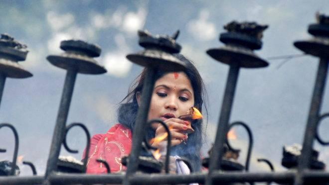 Mulher hindu presta homenagem a Shiva, na Índia.