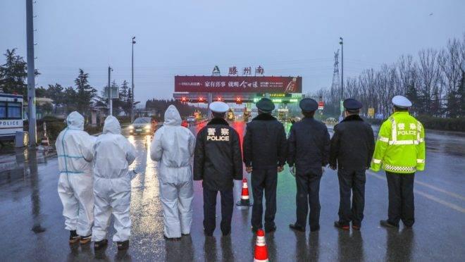 Equipes de saúde usam roupas de proteção para conter a propagação de um vírus letal surgido em Wuhan, China, ao lado de policiais em Tengzou, 27 de janeiro de 2020