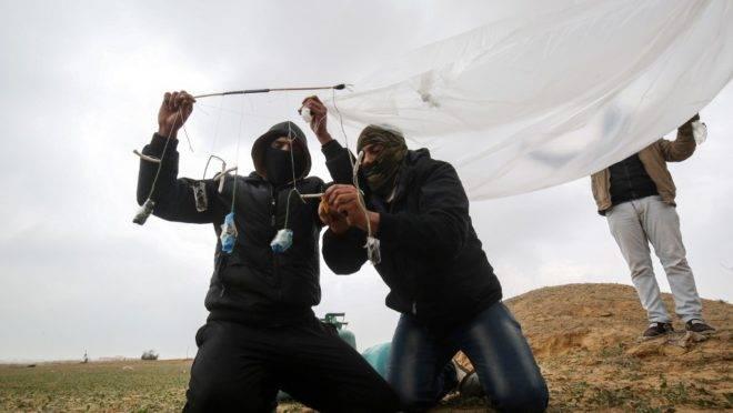 Jovens palestinos mascarados preparam objeto inflamável para ser atirado em território de Israel, perto da fronteira entre Gaza e Israel, 18 de janeiro de 2020