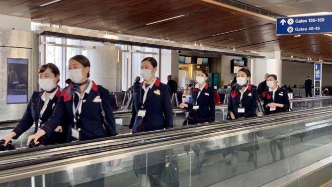 Funcionários da JAL usam máscaras no aeroporto de Los Angeles, EUA, para evitar infecção por coronavírus. A OMS disse que ainda é cedo para dizer o que acontecerá com o surto após queda no número de casos