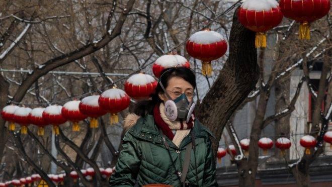Mulher usa máscara para evitar infecção por coronavírus em Pequim, China