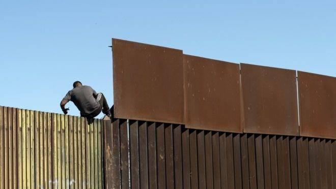 Homem atravessa barreira na fronteira entre México e Estados Unidos, em Mexicali, 11 de fevereiro de 2020