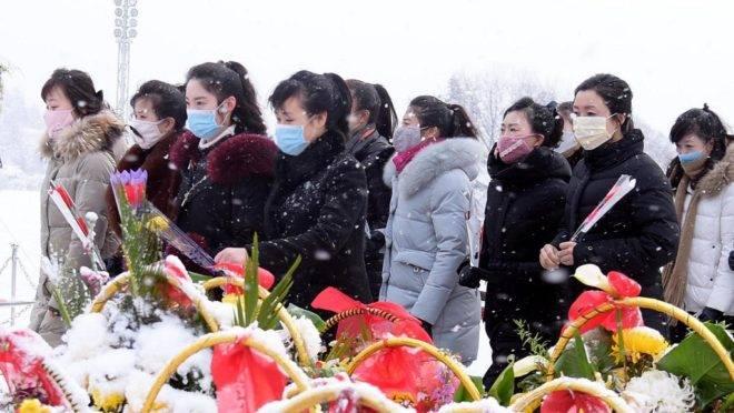 Pessoas em frente às estátuas dos líderes norte-coreanos Kim Il Sung e Kim Jong Il em Pyongyang para celebrar o aniversário de 78 anos de Kim Jong Il, 17 de fevereiro de 2020