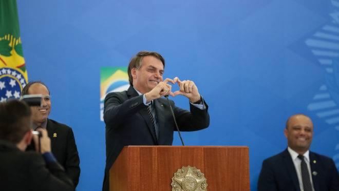 Jair Bolsonaro faz gesto de coração com as mãos em solenidade em 20 de fevereiro de 2020. Lançamento de crédito imobiliário com taxa fixa da Caixa