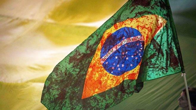 bandeira do Brasil manchada de vermelho.