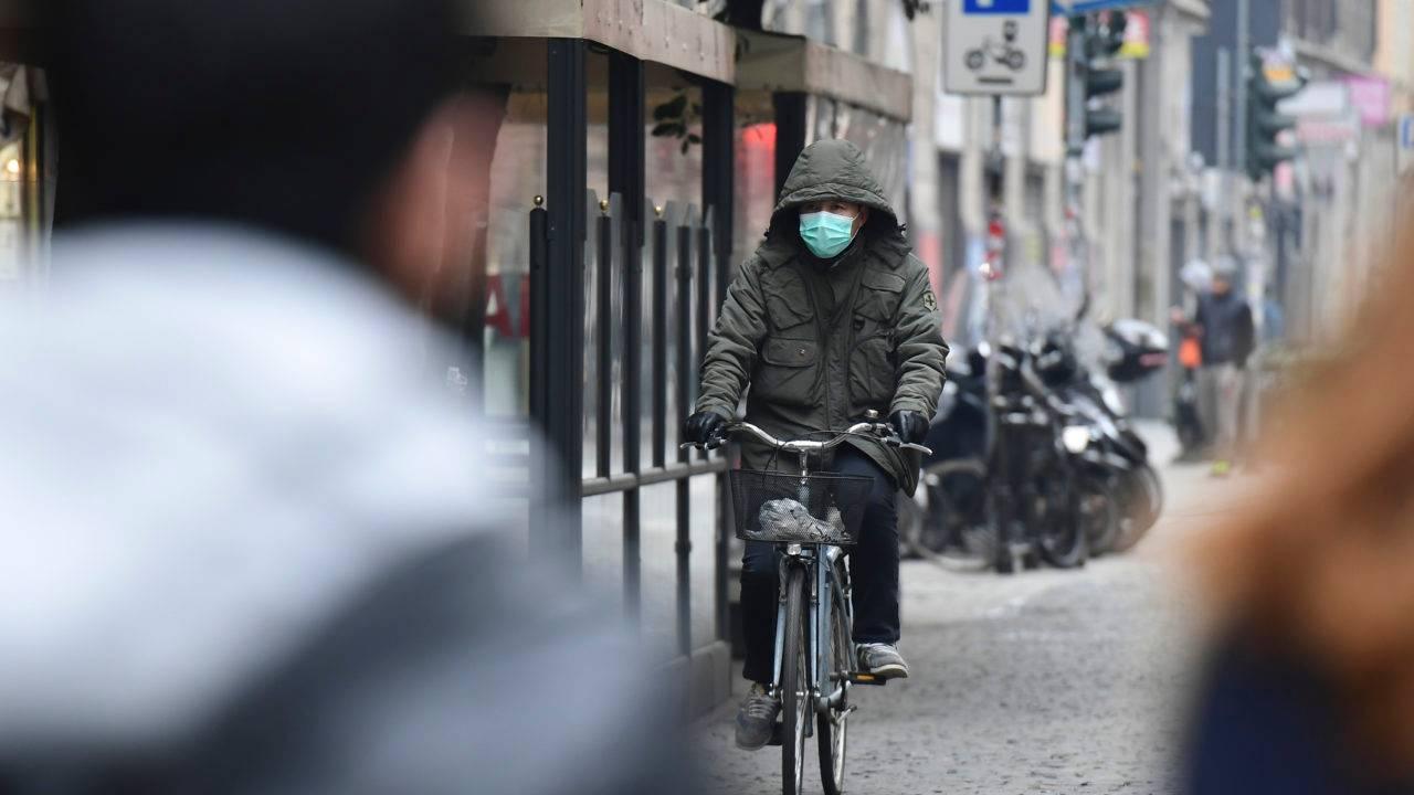 Um homem de máscara respiratória anda de bicicleta em uma rua do distrito chinês de Milão em 25 de fevereiro de 2020.
