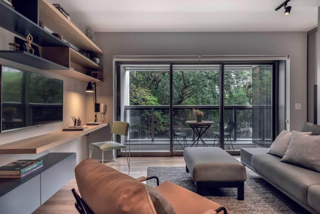 Sala aberta para a varanda traz luz abundante e vista para as copas das árvores. Foto: Escanhuela Fotografias