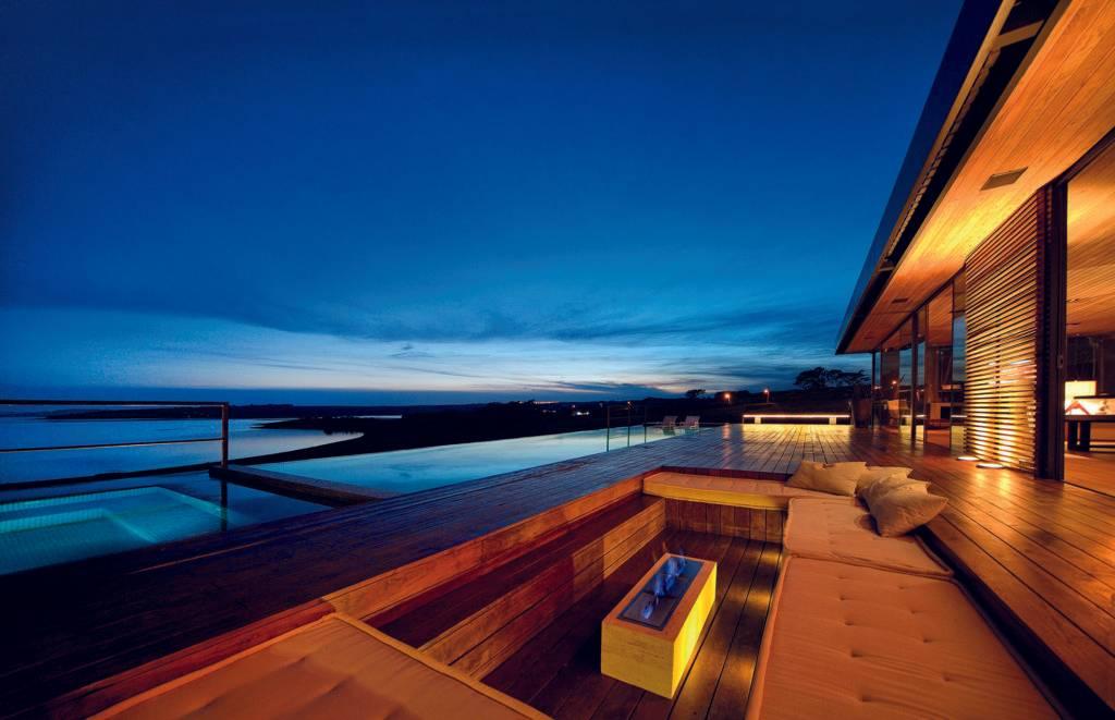 Espaço de convivência se abre para a varanda e piscina à beira do lago. Foto: Fábio Pitrez