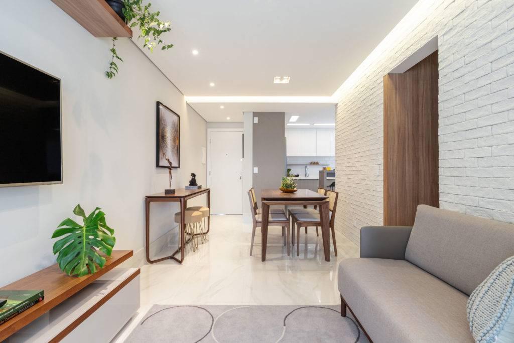 Sala de jantar e estar integradas, com destaque para a parede de tijolinho branco da Kyoto Pedras. Foto: Maura Mello / divulgação.