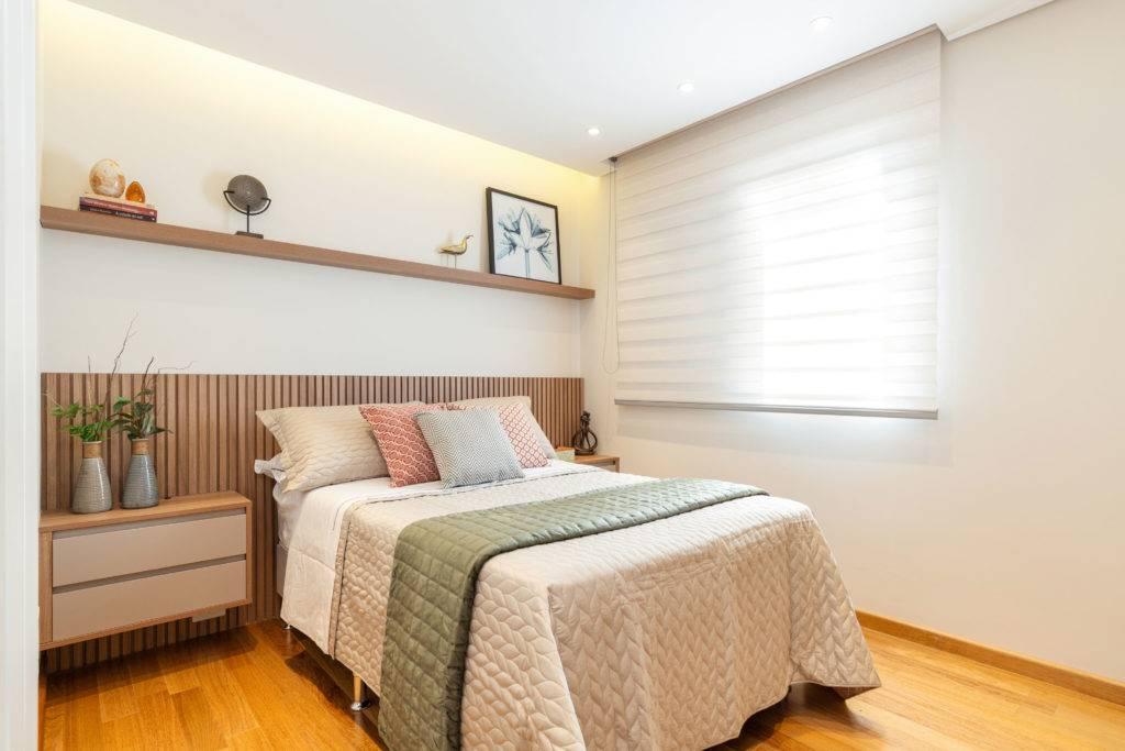 Suíte com piso e rodapés em madeira que trazem a sensação de conforto. O destaque fica para a marcenaria da cabeceira da cama. Foto: Maura Mello / divulgação.