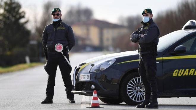 Policiais vigiam entrada em cidade na Itália.