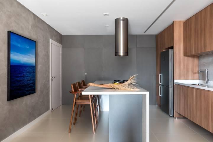 Detalhe da cozinha e da ilha americana, que mistura cinza, textura de cimento queimado e madeira. Foto: Eduardo Macarios
