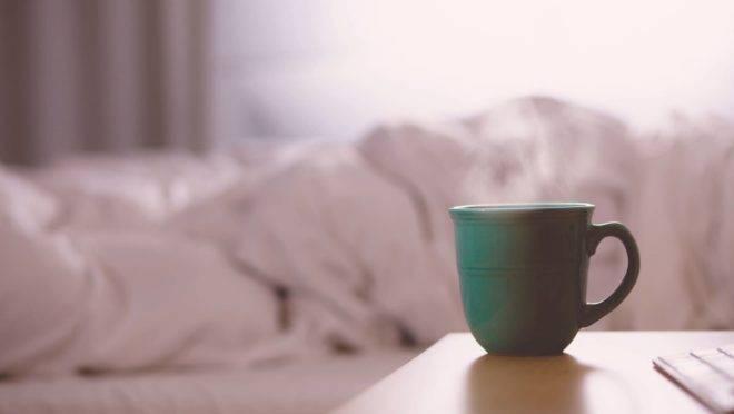 Imagem mostra uma cama aos fundos, com a coberta mexida, e na mesa de cabeceira uma xícara verde de chá.