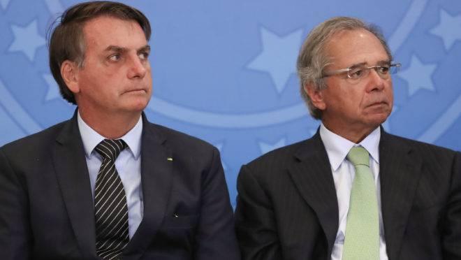O presidente Jair Bolsonaro sentado ao lado do ministro da Economia, Paulo Guedes.