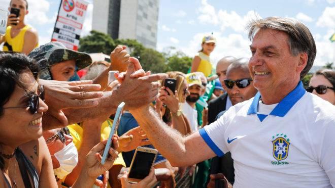 Presidente Jair Bolsonaro cumprimenta manifestantes em frente ao Palácio do Planalto, neste domingo (15).