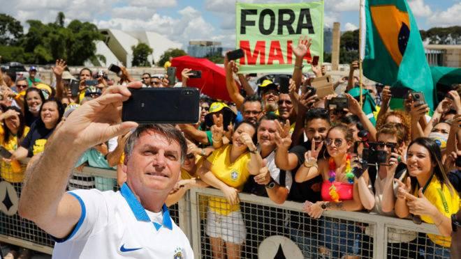 Manifestantes pró-Bolsonaro com faixa contra o presidente da Câmara, Rodrigo Maia.