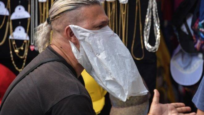 Vendedor ambulante Homem improvisa sacola plástica como máscara para se proteger da pandemia de coronavírus, em São Paulo.