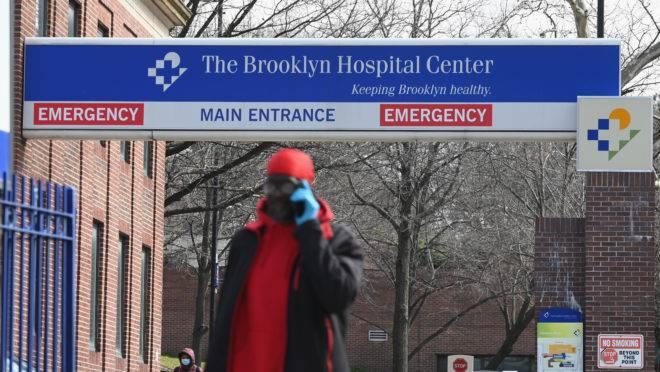 Homem usa máscara facial e luvas de proteção enquanto caminha pela ala de emergência do Brooklyn Hospital Center, em Nova York