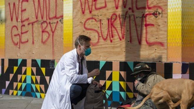 Médico conversa com moradores de rua de São Francisco sobre o coronavírus.