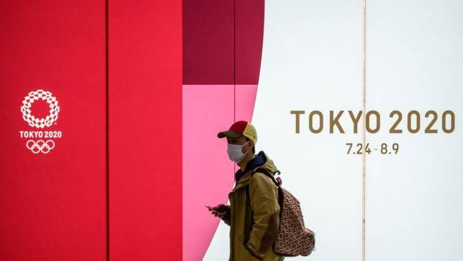Um homem vestindo uma máscara facial entra no túnel de uma estação de metrô com a placa da propaganda oficial dos Jogos Olímpicos de 2020 em Tóquio