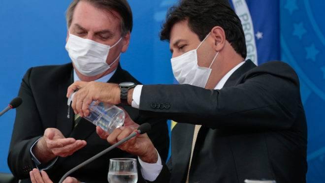 Ministro da Saúde, Luiz Henrique Mandetta, ajuda Jair Bolsonaro a passar álcool em gel.