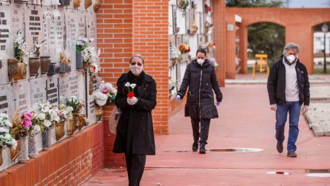 Pessoas usando máscaras chegam ao cemitério Municipal do Sul em Madri, em 23 de março de 2020, para um enterro de uma pessoa que morreu de coronavírus