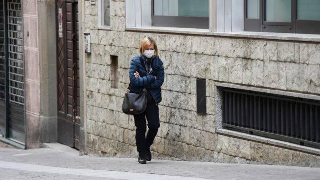Mulher caminha sozinha em rua de Albino, próximo a Bergamo, durante a quarentena italiana devido ao novo coronavírus.