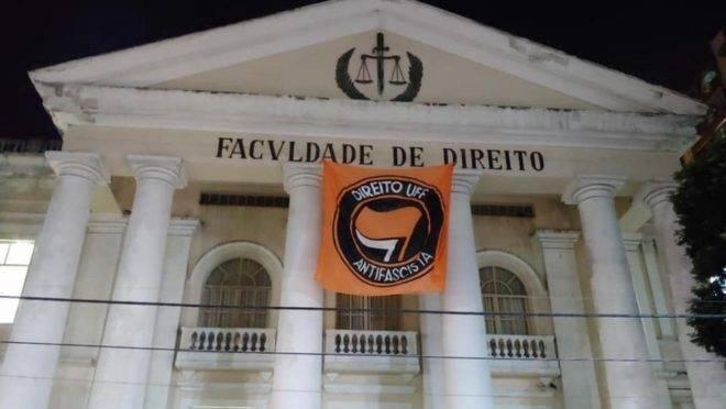 """Nas eleições de 2018, a Justiça ordenou que a Faculdade de Direito daUniversidade Federal Fluminense (UFF) retirasse da fachada uma bandeira em que aparece """"Direito UFF Antifascista""""."""