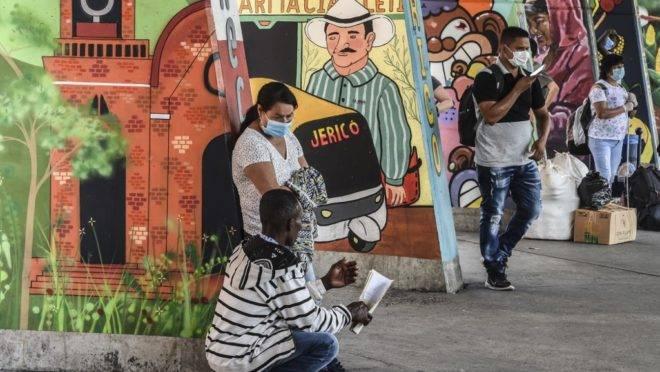 Pessoas usam máscara em terminal de ônibus de Medellín, na Colômbia.