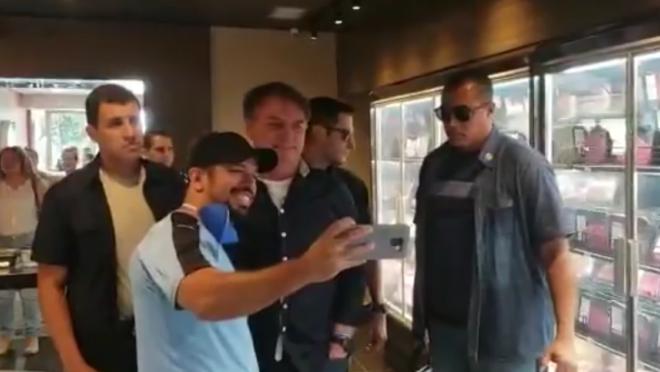 Bolsonaro tira selfie dentro de estabelecimento comercial, durante passeio do presidente em Brasília em meio à pandemia do coronavírus.