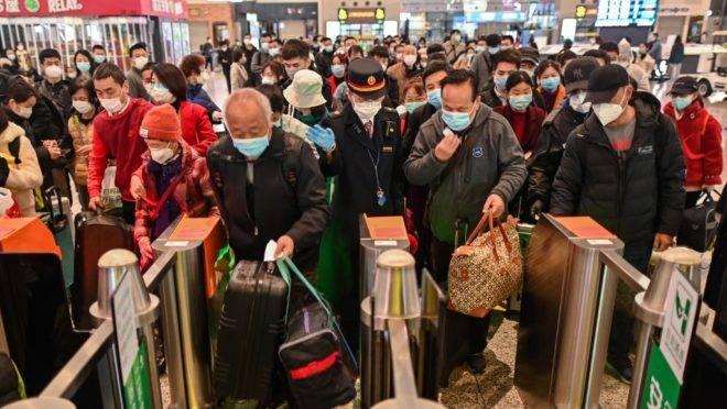 Pessoas em estação de trem em Shangai, China, se dirigem a trem que passa por Wuhan, 28 de março de 2020