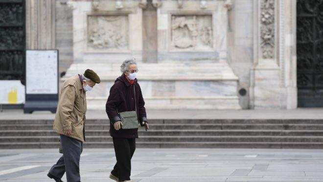 Casal caminha pela deserta praça Duomo, Milão, Itália, 31 de março de 2020, durante lockdown para conter a propagação da infecção do novo coronavírus