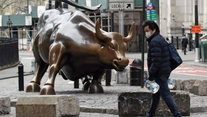 """Morador de Nova York com máscara e galões de água passa pela estátua do """"Touro em Investida"""", de Wall Street. Mais de 92,000 pessoas foram diagnosticadas com coronavírus na cidade"""