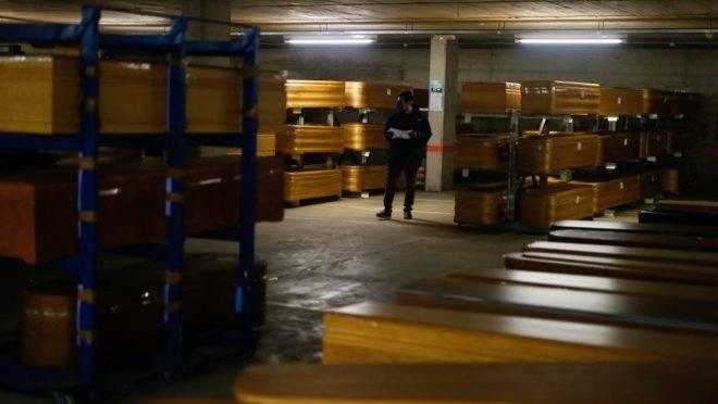 Funcionário verifica caixões, a maioria com corpos de vítimas de covid-19, no estacionamento de uma funerária na região de Barcelona, Espanha. Mais de 900 pessoas morreram na Espanha nas 24 horas anteriores, pelo segundo dia seguido