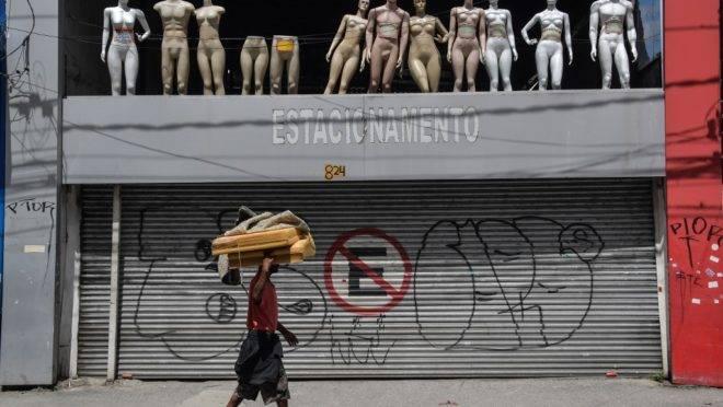 Morador de rua passa em frente a loja fechada em São Paulo, capital.