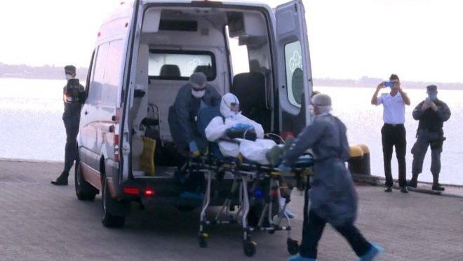 Australiano de 75 anos que estava a bordo do navio australiano Greg Mortimer é transportado para ambulância com sintomas de infecção por coronavírus, 3 de abril. Mais de 80 pessoas a  bordo do navio, ancorado no Uruguai, tiveram resultado positivo para covid-19
