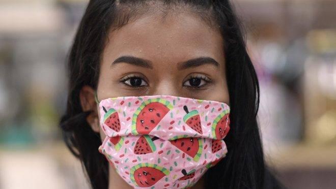 Mulher usa máscara de tecido feita por costureiras da favela Vila Nova São Lucas, Belo Horizonte, 8 de abril. Autoridades de saúde recomendam o uso de máscaras de proteção para população em geral