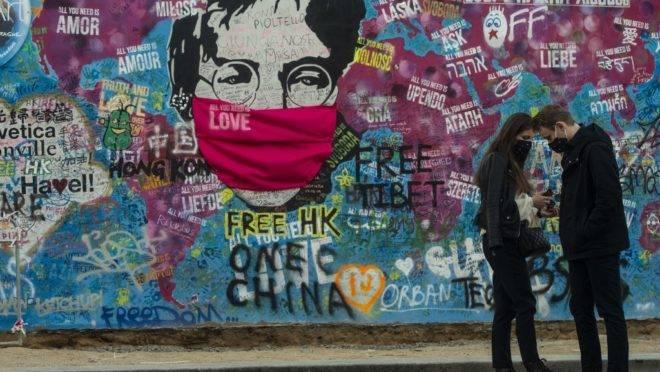 """Casal em frente ao """"Muro do Lennon"""" em Praga, 6 de abril. A maioria das atividades diminuiu ou parou na República Tcheca para conter a propagação da covid-19"""