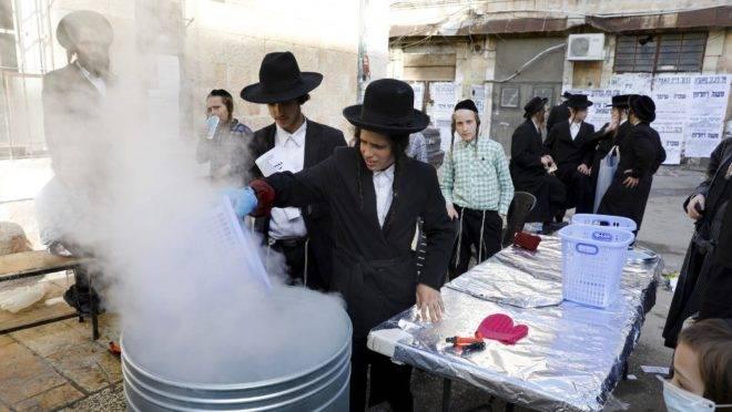 Judeus ultraortodoxos mergulham utensílios de cozinha em água fervente para purificá-los, em preparação antes da Pessach, feriado que celebra a libertação dos hebreus da escravidão no Egito. Jerusalém, 8 de abril de 2020