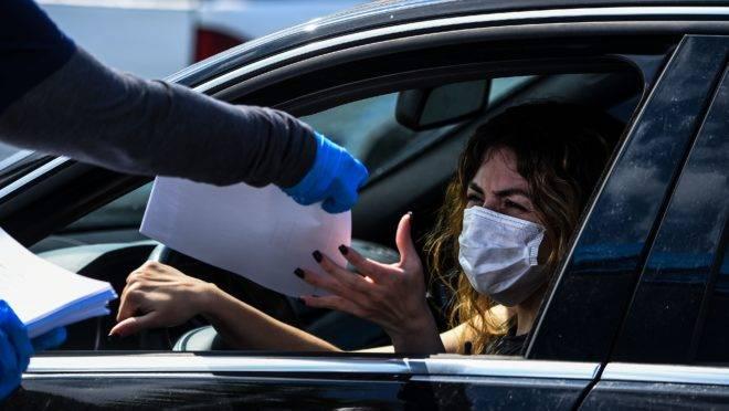 Mulher recebe formulário de seguro-desemprego em um drive-thru na cidade de Hialeah, na Flórida.