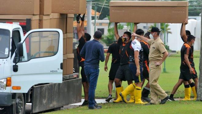 Soldados transportam caixas de papelão que serão usadas como caixões em Guayaquil, no Equador.