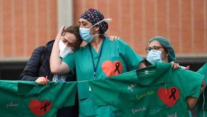 Profissionais de saúde dão apoio à esposa de um enfermeiro que morreu de Covid-19 em hospital na região de Madri, Espanha, 10 de abril. A Espanha registrou o menor número de mortos por coronavírus em 18 dias