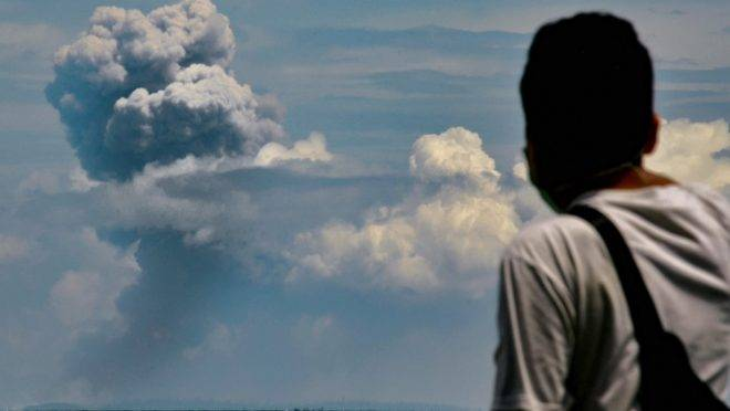Homem observa o vulcão Anak Krakatau durante erupção em Serang, Indonésia, 11 de abril de 2020