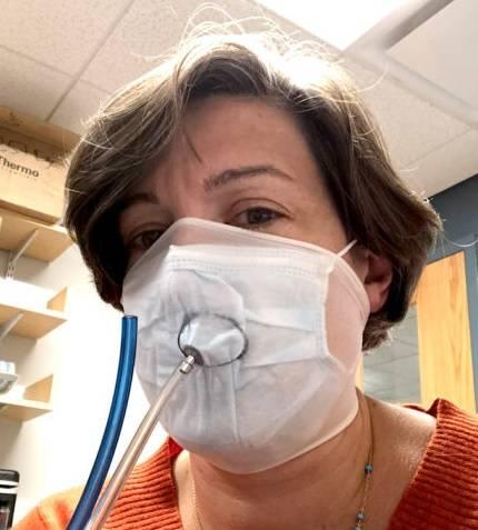 A pesquisadora Loretta Fernandez fazendo uso da máscara com a adição da meia calça por cima e tendo as partículas que passam pelo equipamento testadas. Foto: Universidade de Northeastern